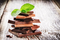 Stack of dark and milk chocolate pieces with mint leaf. On old wood background Stock Image