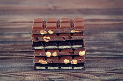 Stack of dark and milk chocolates on wooden table Stock Images