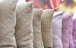 Stack dekorativa kuddar i olika färger på shoppar räknaren fotografering för bildbyråer