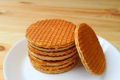 Stack of delectable Stroopwafel or caramel filled Dutch waffle served on white plate on wooden table. Food Background royalty free stock image