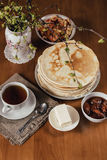 Stack of delicious homemade pancakes or blini, cup of tea, butter. Morning vegetarian breakfast. Stack of delicious homemade pancakes or blini, cup of tea royalty free stock images
