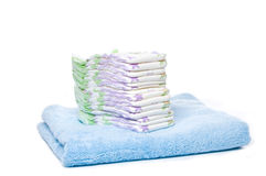 A stack of diapers. On a blue towel with white background Royalty Free Stock Image