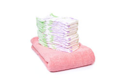 A stack of diapers. On a pink towel with white background royalty free stock images