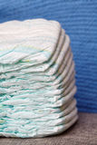 Stack of diapers or nappies on blue knitted background. Closeup Royalty Free Stock Image