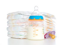 Stack of diapers nipple soother and baby feeding bottle with mil. New born child stack of diapers nipple soother and baby feeding bottle with milk on a white stock photo