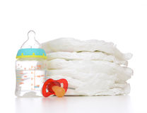 Stack of diapers nipple soother and baby feeding bottle with wat. New born child stack of diapers nipple soother and baby feeding bottle with water on a white royalty free stock image