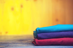 Stack of different cotton t-shirts on wooden table. Fashion, clothing concept Royalty Free Stock Image