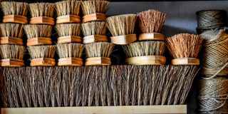 Stack of Wooden Bristle Brushes and Twine. A stack of different sizes of wooden bristle brushes and spools of twine royalty free stock photos