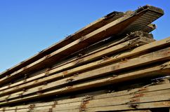 Stack of dimension lumber used for rafters. Rust coated nails stick out of reclaimed dimension wood boards used for rafters Stock Photo