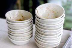 Stack of dirty dishes at a canteen or restaurant. Stack of dirty dishes at a canteen or outdoor restaurant piled high on a white table with remnants of a meal in stock photo