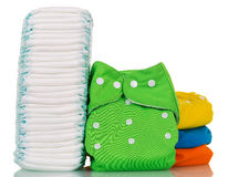 Stack of disposable and cloth diapers isolated on white background. Stock Images