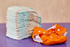 Stack of diapers or nappies on purple background. Stack of disposable diapers or nappies on purple background and reusable one Royalty Free Stock Photos