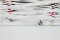 Stack of documents with colorful clips and miniature people Royalty Free Stock Images