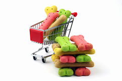 Stack of dog biscuits and shopping cart. Stack of colored dog biscuits and a supermarket shopping trolley royalty free stock photography