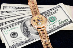 Stack of 100 dollar bills and gold watch on a dark background. Horizontal Royalty Free Stock Photo