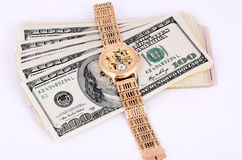 Stack of 100 dollar bills and gold watch on a light background. Horizontal Royalty Free Stock Photos