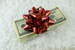 A stack of dollar bills and a red gift bow in the fake snow stock image