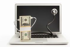 Stack of dollar bills with stethoscope on laptop Stock Photos