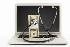 Stack of dollar bills with stethoscope on laptop Royalty Free Stock Photo