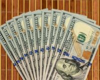 The stack is 100 dollar bills USD spread out like a fan, on a wooden background.  stock photos
