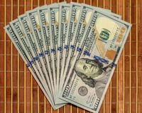 The stack is 100 dollar bills USD spread out like a fan, on a wooden background.  stock images