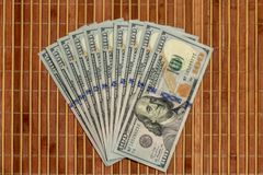 The stack is 100 dollar bills USD spread out like a fan, on a wooden background. The stack is 100 dollar bills USD spread out like a fan, on a wooden background royalty free stock photo
