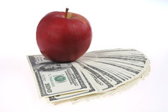 Stack of dollars lays near an apple Royalty Free Stock Photo