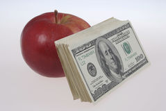 Stack of dollars lays near an apple Royalty Free Stock Photos