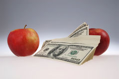 Stack of dollars lays near two apples Royalty Free Stock Photos