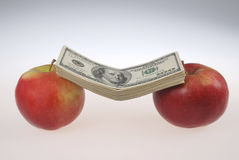 Stack of dollars lays on two apples Stock Photo