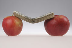 Stack of dollars lays on two apples Royalty Free Stock Images