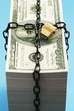 Stack of Dollars secured by padlock and chain Royalty Free Stock Images