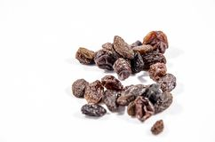 A stack of dried grapes or better know as raisins. A raisin is a dried grape. Raisins are produced in many regions of the world and may be eaten raw or used in Royalty Free Stock Images