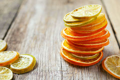 Stack of dried orange and lemon slices on wooden table. Royalty Free Stock Images