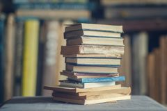 A stack of dusty shabby books. In front of blurry shelves Royalty Free Stock Image