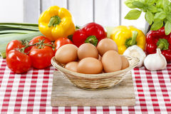 Stack of eggs, fresh vegetables in the background Royalty Free Stock Images