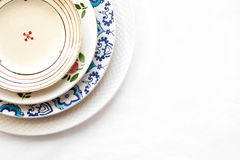 Stack of empty ceramic plates isolated on white. Background with copy space. Cheerful colorful dishes decorated with floral pattern. Beautiful vintage crockery Royalty Free Stock Photos