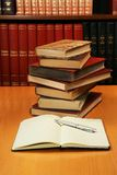 Stack of encyclopedia books. And a diary notebook in a library Royalty Free Stock Photo