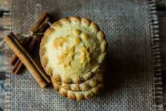 Stack of English mince pies on burlap cloth with cinnamon sticks, on a vintage wood box, top view, flat lay, close up Royalty Free Stock Photo