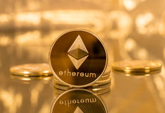 Stack of ethereum coins with gold background. Stack of ether coins or ethereum on gold background to illustrate blockchain and cyber currency royalty free stock photography