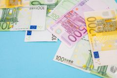 Stack of Euro bank notes on blue background in the studio with space for text.  royalty free stock photography