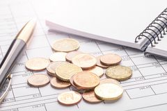 Stack of euro euro coins on old black wooden table. Pen, notebook and accounting documents with numbers stock photos