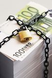 Stack of Euros secured by padlock and chain Stock Photo