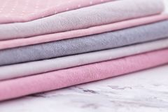 Stack of fabrics over marble table Royalty Free Stock Photos