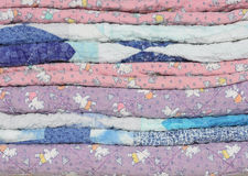 Stack of Faded, Worn Children's Quilts. A stack of faded, fraying and worn handmade purple, blue and pink children's quilts Stock Photography