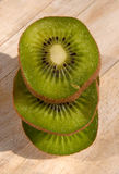 Stack of kiwi slices on a wooden board Royalty Free Stock Images