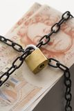 Stack of fifty pound notes secured by padlock and chain Stock Photos