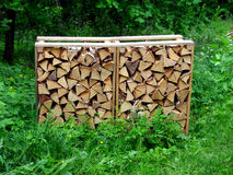 Stack of firewood. A neat stack of firewood in the green garden Royalty Free Stock Photos