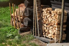 Stack of firewood next to old wooden cottage wall, sun lit grass royalty free stock photo