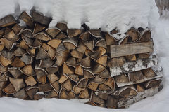 Stack of firewood under snow. birch firewood. close up. Stock Photos